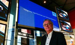 Dagvoorzitter Pieter Meijers (en vice-voorzitter van de vakgroep) toont de nieuwe  naam van de Vakgroep Lichtreclame: Vakgroep SignTechniek.